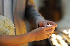 Iluminação da noiva e do noivo acima de uma vela Fotografia de Stock Royalty Free
