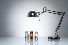 Iluminar-se acima da garrafa droga a medicina do comprimido com lâmpada de mesa Foto de Stock