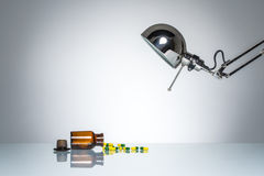 Iluminar-se acima da garrafa droga a medicina do comprimido com lâmpada de mesa Fotos de Stock Royalty Free