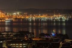 Iluminate das luzes alaranjadas o porto de Seattle e de Elliott Bay na noite imagem de stock