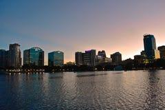 Iluminated街市大厦在湖在美好的五颜六色的日落背景的Eola边 免版税库存照片