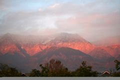 Iluminated and Aflame Himalayas, Kangra India. The seismic zone of Dhauladhar Himalayan ranges come alive and aflame with winter sunsets in Scenic Kangra Valley Royalty Free Stock Image