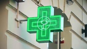 Iluminated Green Pharmaceutical Cross. Pharmacy Shop green cross rack focus stock video