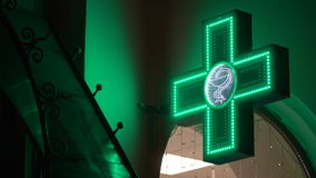 Iluminated Green Pharmaceutical Cross. Pharmacy Street Sign stock video footage