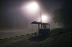 Iluminazioni pubbliche nebbiose nebbiose con la strada abbandonata notte Fotografie Stock