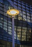 Iluminująca latarnia uliczna przeciw budynkowi biurowemu przy nocą obraz stock