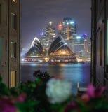 Iluminująca opera przy nocą w budynki obramiający, projektów metaforyka, Zdjęcia Stock