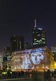 Iluminujący budynki z projekcją papierowy pieniądze przy nocą du Obrazy Royalty Free