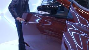 Iluminujący futurystyczny samochód, mężczyzna dostaje inside, wystawa wyłączni pojazdy zbiory wideo