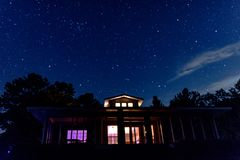 Iluminujący do domu i nocne niebo Fotografia Stock