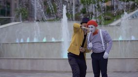 Magician showing magic trick to a mime with playing card. Ilusionist and mime have fun standing near the illuminated fountains at the urban street. Two street stock video