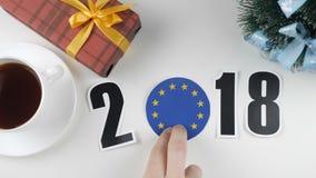 A ilustração, ano novo, a mão masculina pôs sobre a tabela uma bandeira da União Europeia, bola cauntry, 2018 ilustração stock
