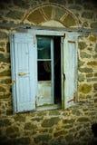 Ilustración nostálgica, obturadores azules descolorados de la ventana en la casa abandonada, Grecia imagen de archivo