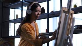 Ilustraciones de dibujo del pintor de sexo femenino creativo en el estudio almacen de video
