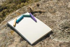 Ilustraciones del primer para el diseñador Una libreta en blanco para el pastel de dibujo en el cual la endecha los creyones en c Foto de archivo libre de regalías