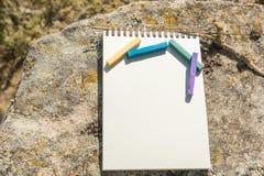Ilustraciones del primer para el diseñador Una libreta en blanco para el pastel de dibujo en el cual la endecha los creyones en c Fotos de archivo