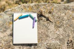 Ilustraciones del primer para el diseñador Una libreta en blanco para el pastel de dibujo en el cual la endecha los creyones en c Imagen de archivo libre de regalías