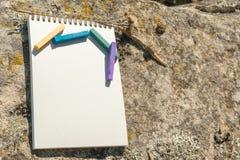 Ilustraciones del primer para el diseñador Una libreta en blanco para el pastel de dibujo en el cual la endecha los creyones en c Foto de archivo