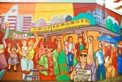 Ilustraciones en pintada de la pared con la muchedumbre de inmigrantes que protestan para sus derechas Imagen de archivo libre de regalías