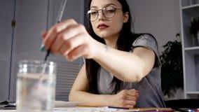 Ilustraciones femeninas del dibujo del artista en casa con el cepillo almacen de metraje de vídeo