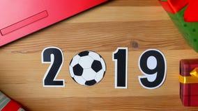 Ilustracja, nowy rok, męska ręka stawia dalej stół na piłki nożnej piłce, 2019