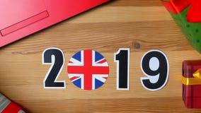 Ilustracja, nowy rok, męska ręka stawiająca dalej stół na Brytyjski flaga, kraj piłka, 2019