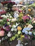ilustracji sklepu smellcomp kwiat Jaskrawych kwiatów i zielonych rośliien stojak pakował w garnkach na półkach i tacach w sklepie Zdjęcie Royalty Free