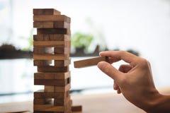 Imágenes de la mano de los empresarios que ponen y que tiran del bloque de madera Foto de archivo
