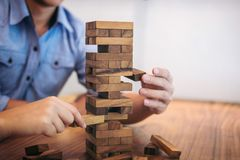 Imágenes de la mano de los empresarios que ponen y que tiran del bloque de madera Fotos de archivo