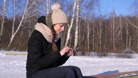 Imágenes de la ojeada de la mujer, texto, número en Smartphone en el bosque del invierno, Sunny Day almacen de metraje de vídeo