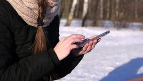 Imágenes de la ojeada de la mujer, texto, número en Smartphone en el invierno Sunny Day almacen de video