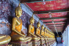 Imágenes de oro hermosas de Buda en el pasillo en el templo de Wat Suthat, Fotografía de archivo