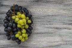Imágenes de uvas negras en imágenes de madera en la placa, las grandes uvas negras del piso, negras y verdes de las uvas Fotografía de archivo libre de regalías