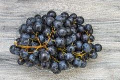 Imágenes de uvas negras en imágenes de madera en la placa, las grandes uvas negras del piso, negras y verdes de las uvas Fotos de archivo