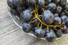 Imágenes de uvas negras en imágenes de madera en la placa, las grandes uvas negras del piso, negras y verdes de las uvas Imagenes de archivo