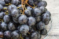 Imágenes de uvas negras en imágenes de madera en la placa, las grandes uvas negras del piso, negras y verdes de las uvas Foto de archivo