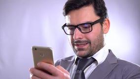 imágenes de vídeo 4k de un hombre joven usando un teléfono móvil contra un fondo gris Siempre en tacto Tenencia sonriente del hom almacen de metraje de vídeo