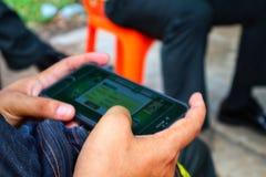 Imágenes del primer de la gente que sostiene los teléfonos, iPhone, jugando a los juegos onlines, diversión imagen de archivo