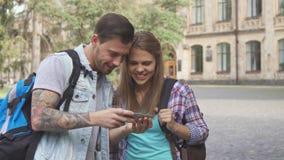 Imágenes del reloj de los estudiantes en smartphone en campus imágenes de archivo libres de regalías