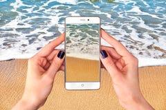 Imágenes del Takin en el teléfono elegante en la playa fotos de archivo