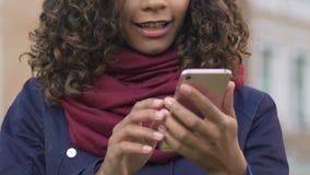 Imágenes multirraciales jovenes de la ojeada de la mujer en el smartphone, charlando con el amigo almacen de metraje de vídeo