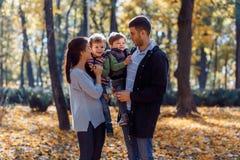 Imágenes naturales de una familia de cuatro miembros feliz que tiene outsiade de la diversión en un día soleado del otoño Concept foto de archivo libre de regalías