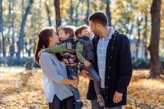 Imágenes naturales de una familia de cuatro miembros feliz que tiene outsiade de la diversión en un día soleado del otoño Concept imagen de archivo