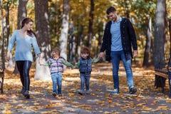 Imágenes naturales de una familia de cuatro miembros feliz que tiene outsiade de la diversión en un día soleado del otoño Concept imagen de archivo libre de regalías