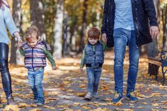Imágenes naturales de una familia de cuatro miembros feliz que tiene outsiade de la diversión en un día soleado del otoño Concept imágenes de archivo libres de regalías