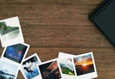 Imágenes polaroid y un álbum de foto espiral negro en una tabla de madera con el espacio blanco imagen de archivo libre de regalías