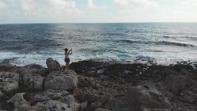 Imágenes que toman femeninas jovenes que se colocan en roca grande cerca del océano con las ondas fuertes Tiro aéreo del abejón d