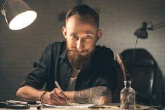Imágenes salientes del dibujo del hombre joven en el escritorio Foto de archivo