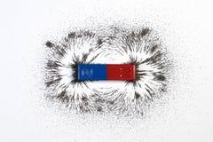 Imán o la física de barra rojo y azul magnética con el mag del polvo del hierro imágenes de archivo libres de regalías