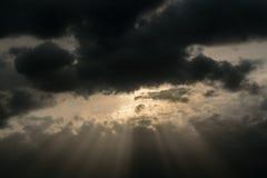 Im Abendhimmel durch die Regenwolken lugt die Sonne heraus Von der Sonne laufen die Sonne ` s Strahlen auseinander Lizenzfreie Stockbilder